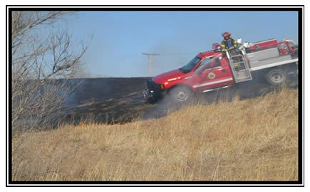 A fire truck drives through prairie grass to help with a controlled burn